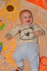 Baby Cranio-Sacral Behandlung/Therapie, lachendes Baby auf einer Spieldecke