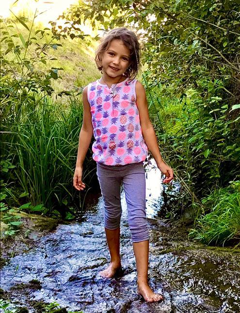 KINDER Cranio-Sacral Behandlung/Therapie, Mädchen steht in einem Bach mit Wasser
